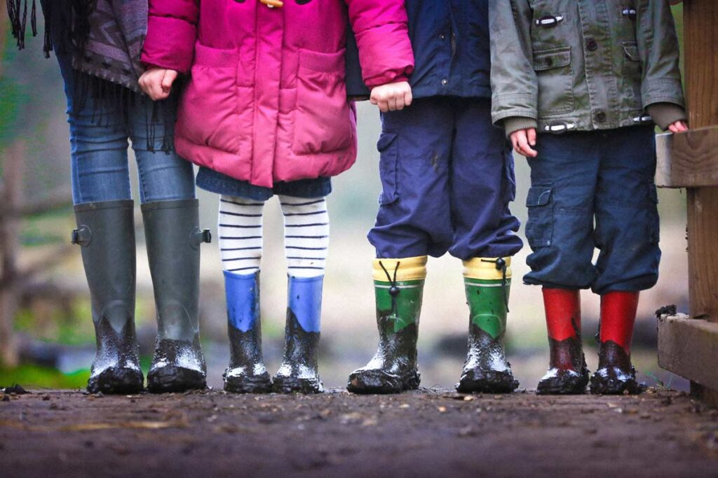 Four kids in a row wearing rain gear seen from shoulders to welly boots