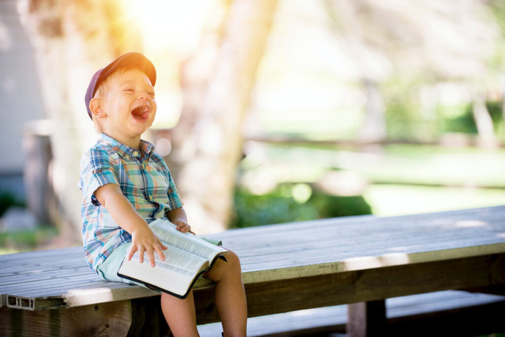 A child laughing on a bench with a book in his hand