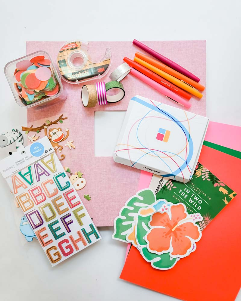The materials needed for a DIY birthday photobook project: prints, stickers and a scrapbook