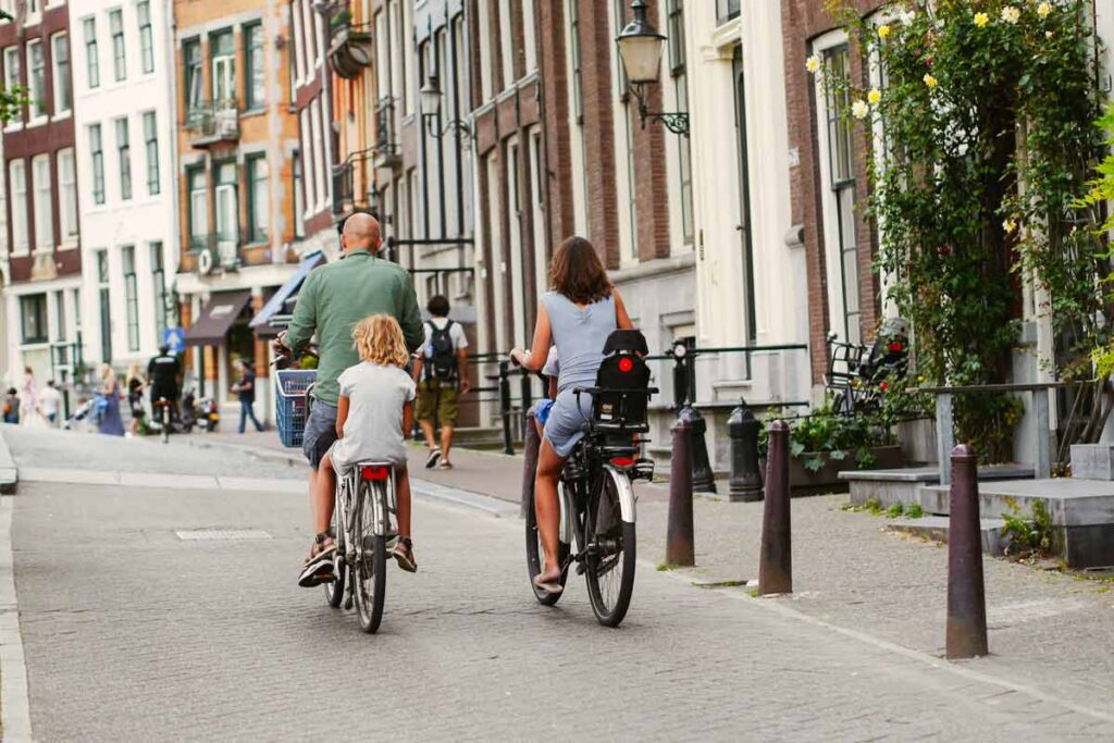 On the back of her dad's bike a child rides to her first day of school with her family.