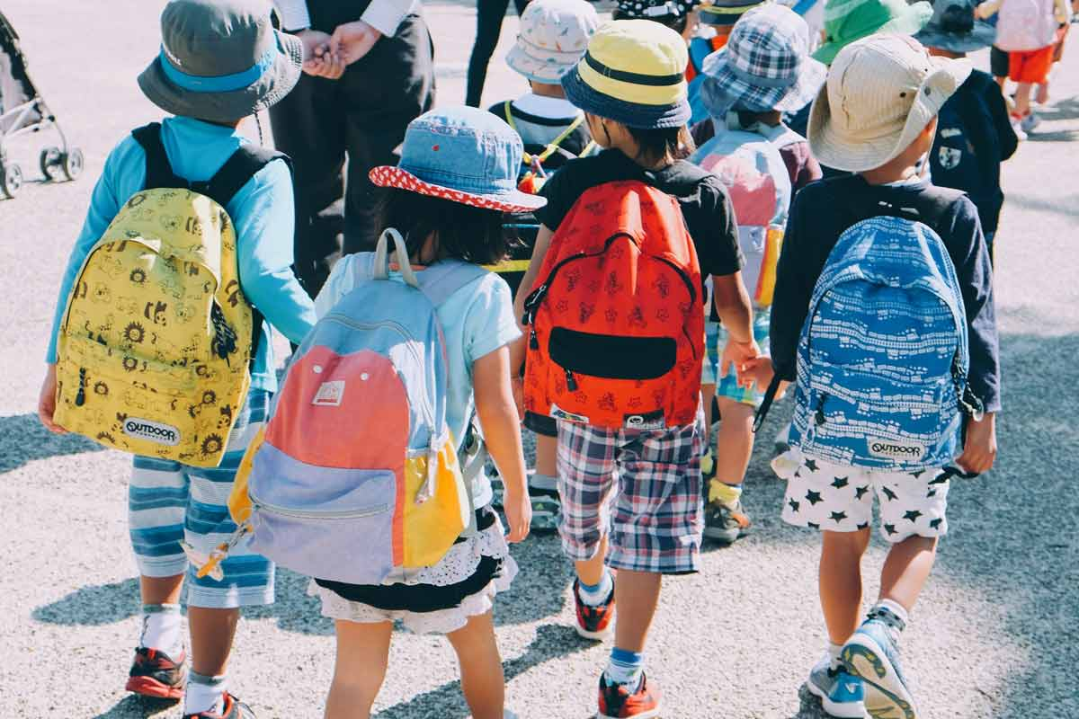 A group of children head to their first day of school, each wearing a bright backpack
