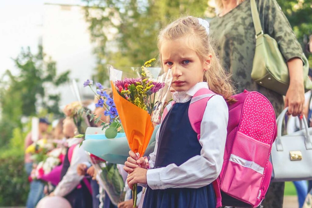 A little girl receives a bouquet of flowers as a first day of school tradition