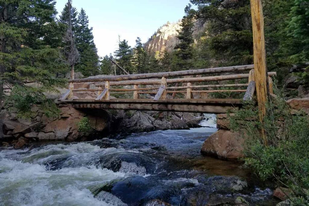 A bridge across a rocky river surrounded by trees