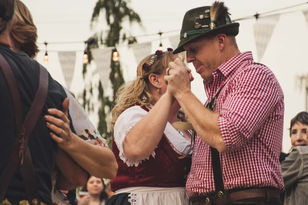 A traditional couple dancing in German tracht during Oktoberfest
